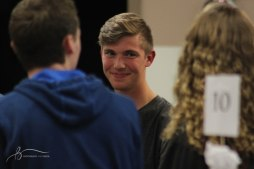 A group of students laugh and play the game of signs at Cru Fall Retreat.