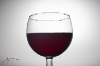 A glass of wine sits on the light table in the photojournalism studio on Sunday, March 26, 2017. || Becca Tapp © 2017