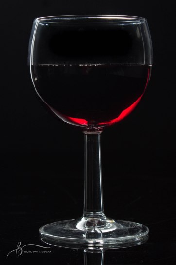 A glass of wine sits on and in front of a black surface on Sunday, March 26, 2017. || Becca Tapp © 2017